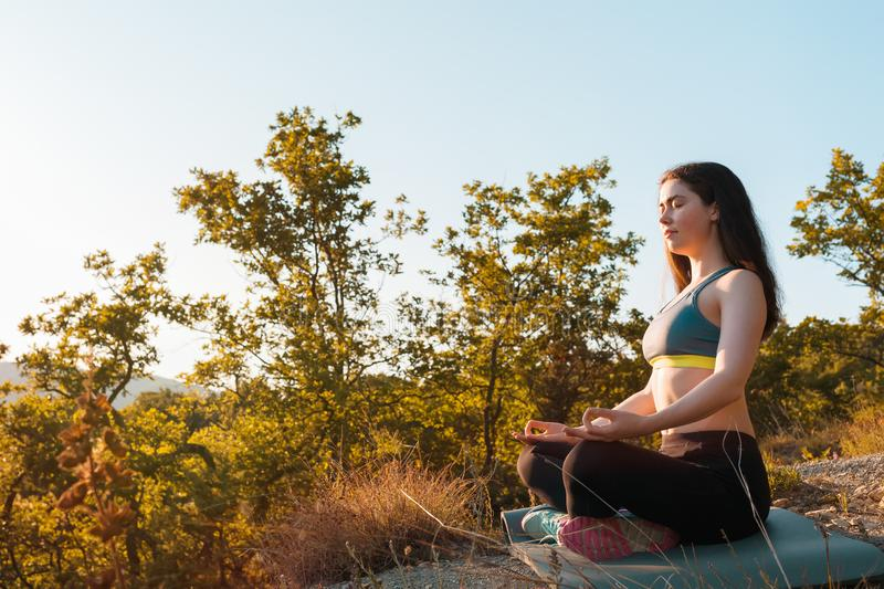 Young beautiful woman doing yoga and meditating in the Park. The concept of yoga, sports and meditation. Copy space stock image