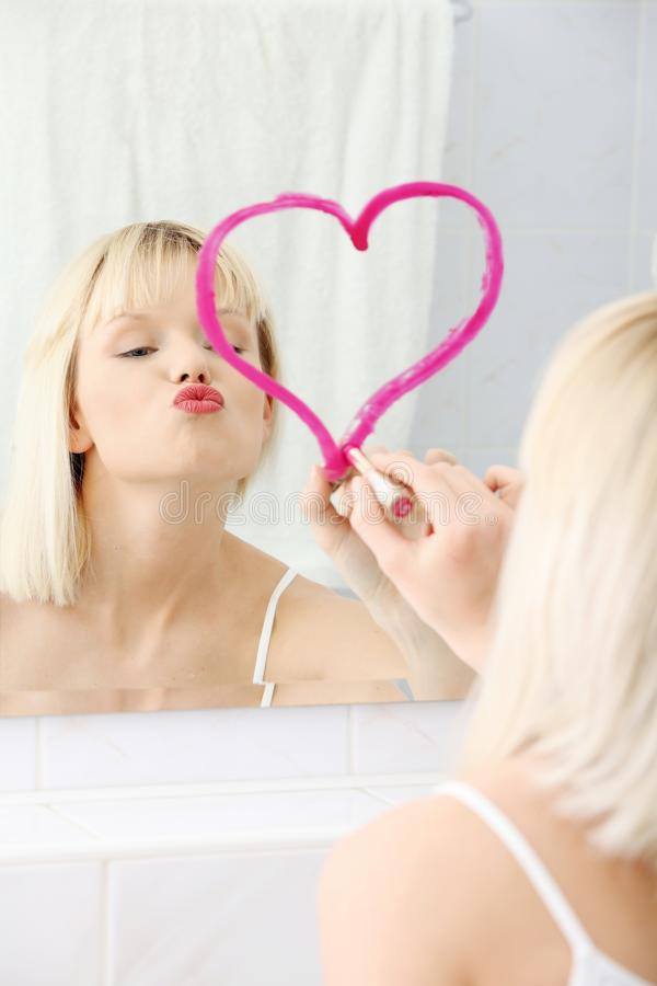 Young beautiful woman drawing big heart on mirror. royalty free stock photo