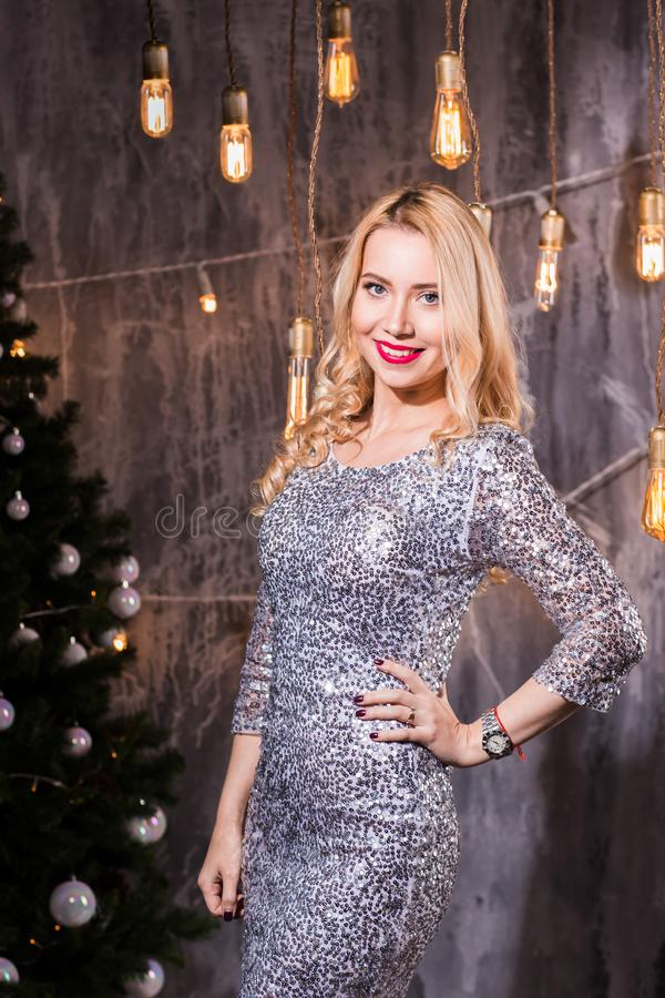Young beautiful woman in dress on christmas with red lips, woman in holiday room with a Christmas tree and xmas balls. Happy new year royalty free stock images