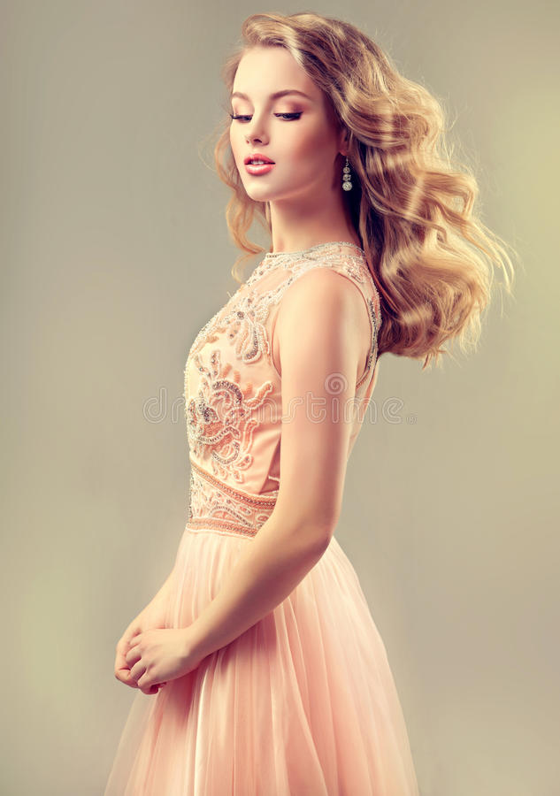 Young beautiful woman, dressed in evening gown. Loose,wavy hair and bright make up stock image