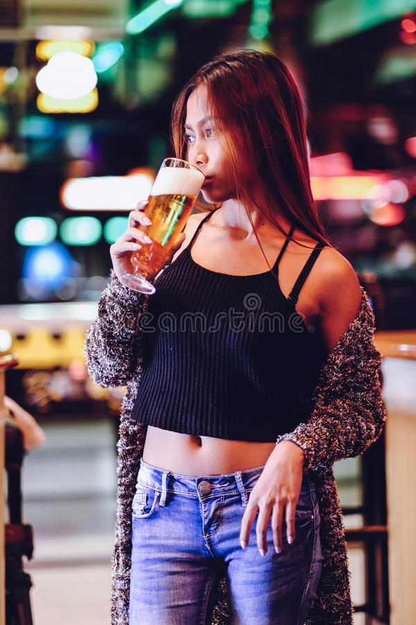 Young beautiful woman drinking beer in a bar stock image
