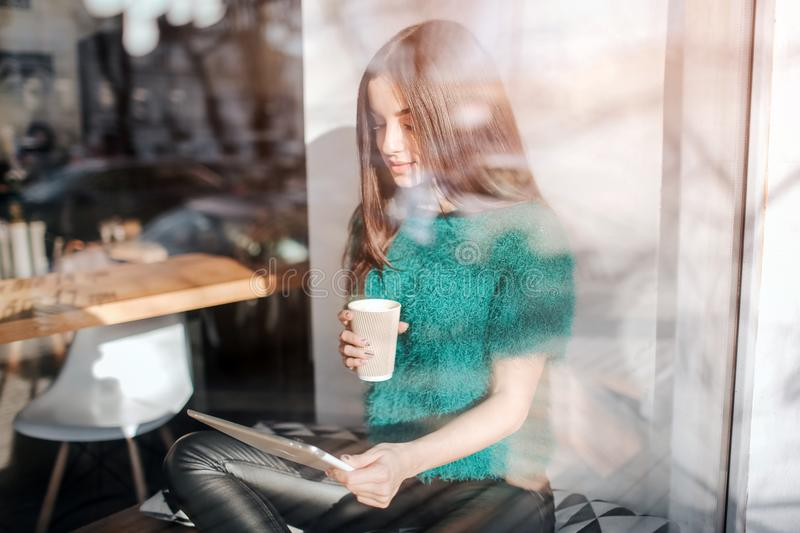 Young beautiful woman drinking coffee at cafe bar. Female model Young using digital tablet at cafe royalty free stock photo