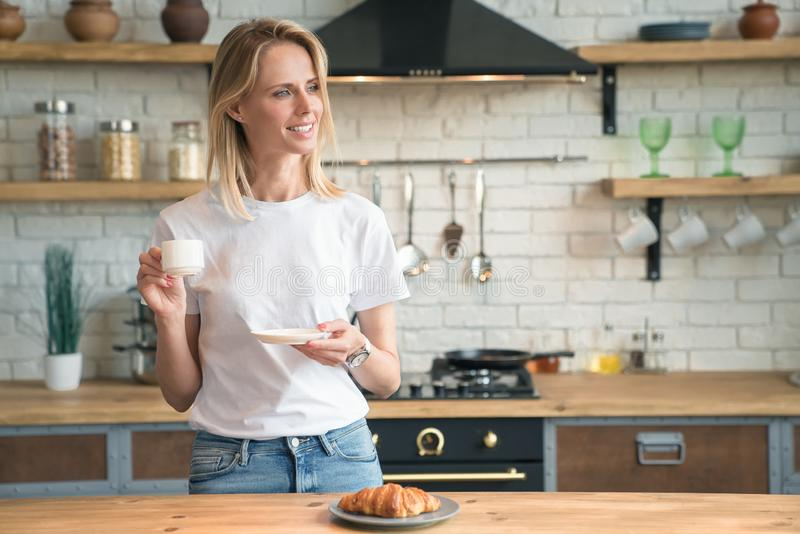 Young beautiful woman is drinking coffee in the kitchen in the morning and smiling looking sideways. Wearing white shirt and jeans royalty free stock photos