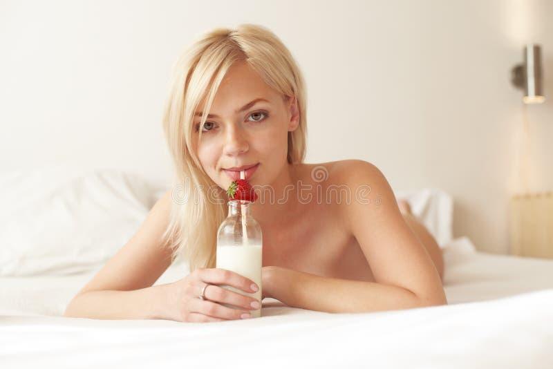 Young beautiful woman drinking milk stock photo