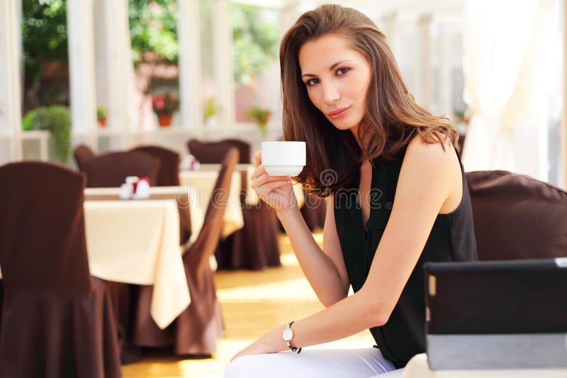 Young beautiful woman drinks coffee in cafe stock photography