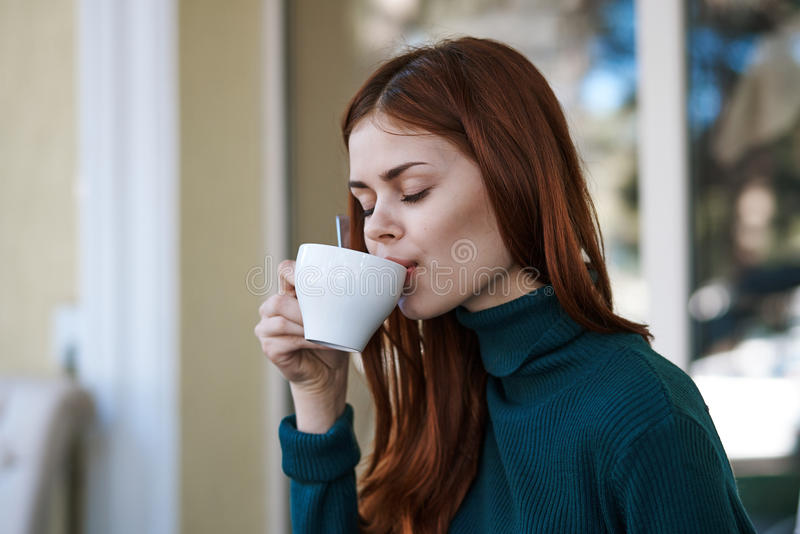 Young beautiful woman drinks coffee in a cafe on a street in winter stock image