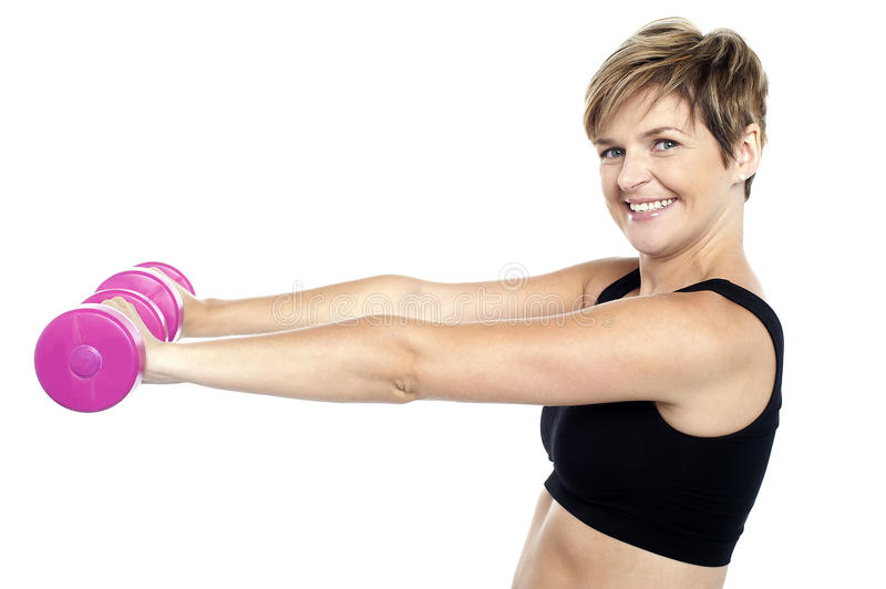 Young beautiful woman with dumbbells in hands royalty free stock photo