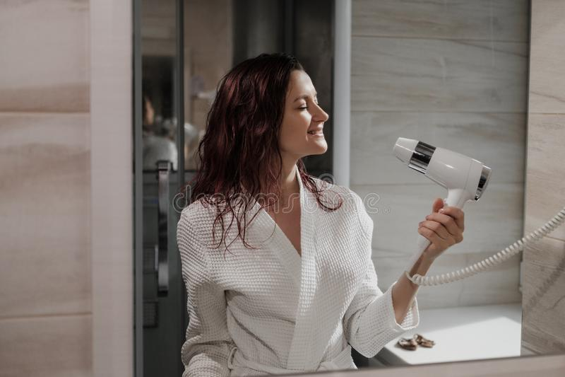 Young beautiful woman with dyed hair in white bathrobe in bathroom dries hair with hairdryer and smiles. stock images