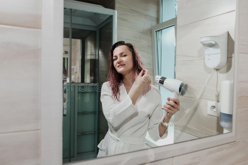 Young beautiful woman with dyed hair in white bathrobe in bathroom dries hair with hairdryer and smiles. Young beautiful woman with dyed hair in a white royalty free stock photos