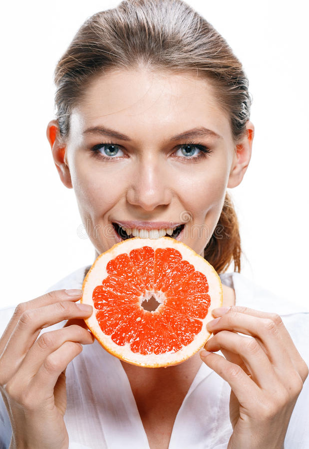 Young beautiful woman eat grapefruit isolated on white background. Good looking girl of the european appearance biting a cut piece of grapefruit - isolated on stock image