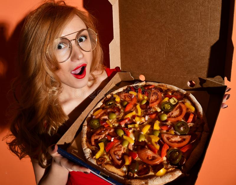 Young beautiful woman eat mexican vegetarian whole pizza in box on orange stock photos