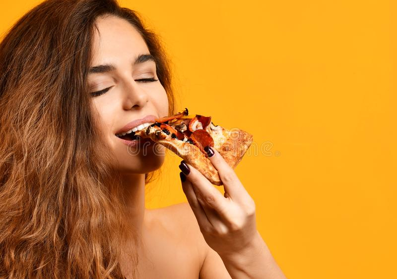 Young beautiful woman eat slice of pepperoni pizza with closed eyes smiling on yellow stock photos