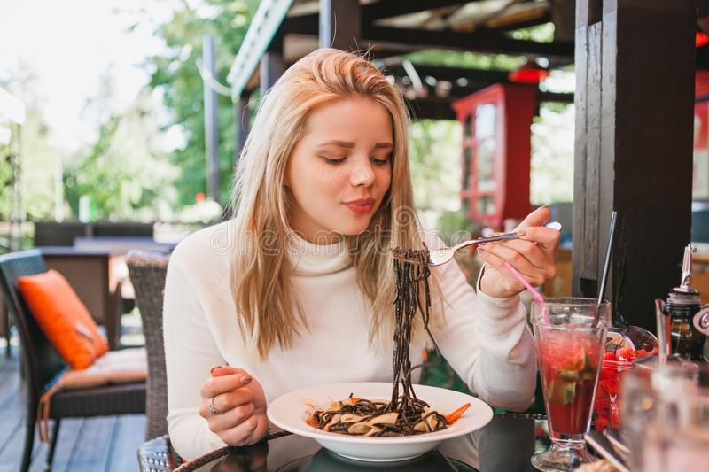Young beautiful woman eating black pasta with seafood and cuttlefish ink in the outdoor restaurant. Funny and beautiful. Concept beauty and tasty food royalty free stock images