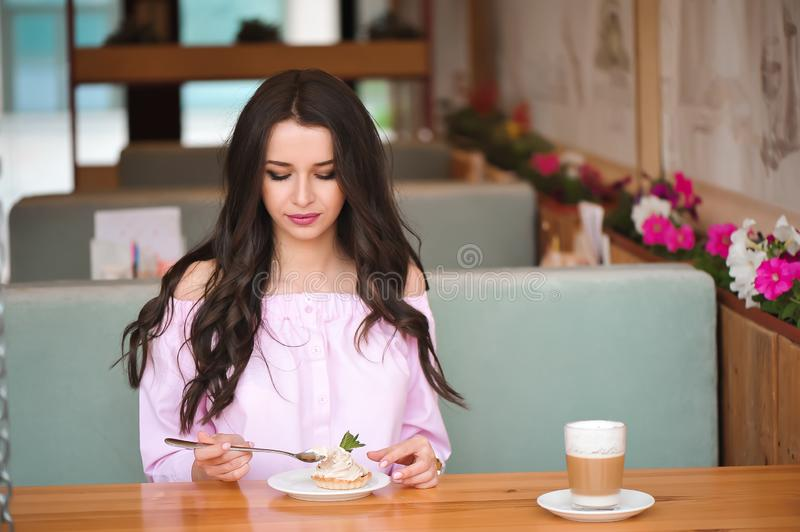 Young beautiful woman eating a dessert in a cafe. Young beautiful woman eating a dessert royalty free stock photo