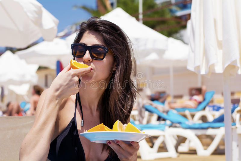 Young beautiful woman eating fresh orange fruit at the beach stock photo