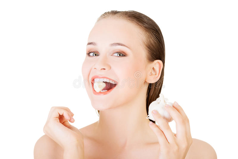 Young beautiful woman eating garlic. Healthy eating concept. stock photo