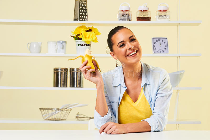 Young beautiful woman eating healthy banana in the kitchen. Banana fruit eating snack yellow health healthy diet peel split weight loss chewing bite royalty free stock photos