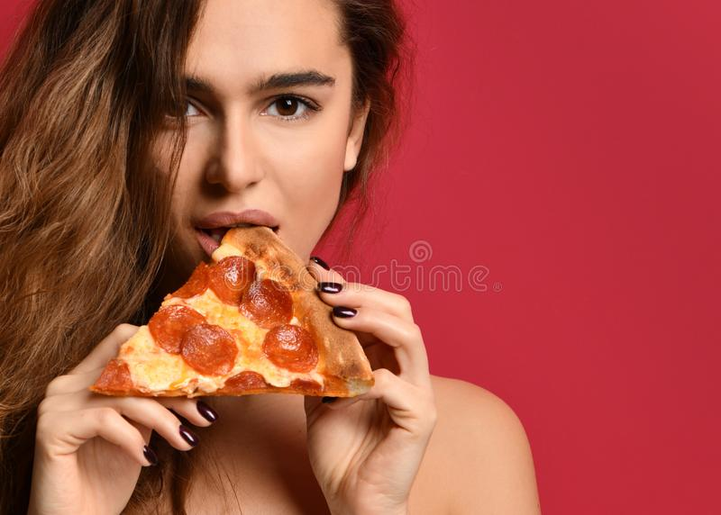 Young beautiful woman eating slice of pepperoni pizza on pink red stock photo
