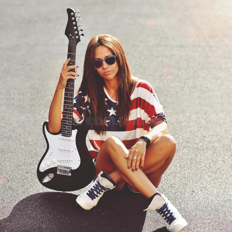 Young beautiful woman with electric guitar - outdoors royalty free stock images