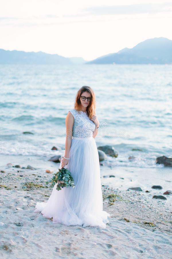 Young beautiful woman in elegant blue dress holding the bouquet of flowers and walking near the Garda lake, Sirmione. Lago di Gard. A, Italy stock images