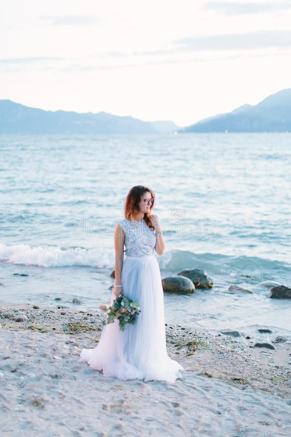 Young beautiful woman in elegant blue dress holding the bouquet of flowers and walking near the Garda lake, Sirmione. Lago di Gard. A, Italy stock photography