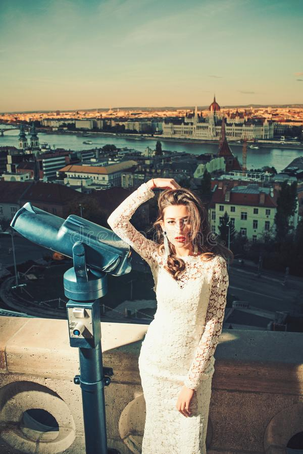 Young beautiful woman enjoy view with binoculars. Water and sky is blue. Girl wears white dress.  stock photo
