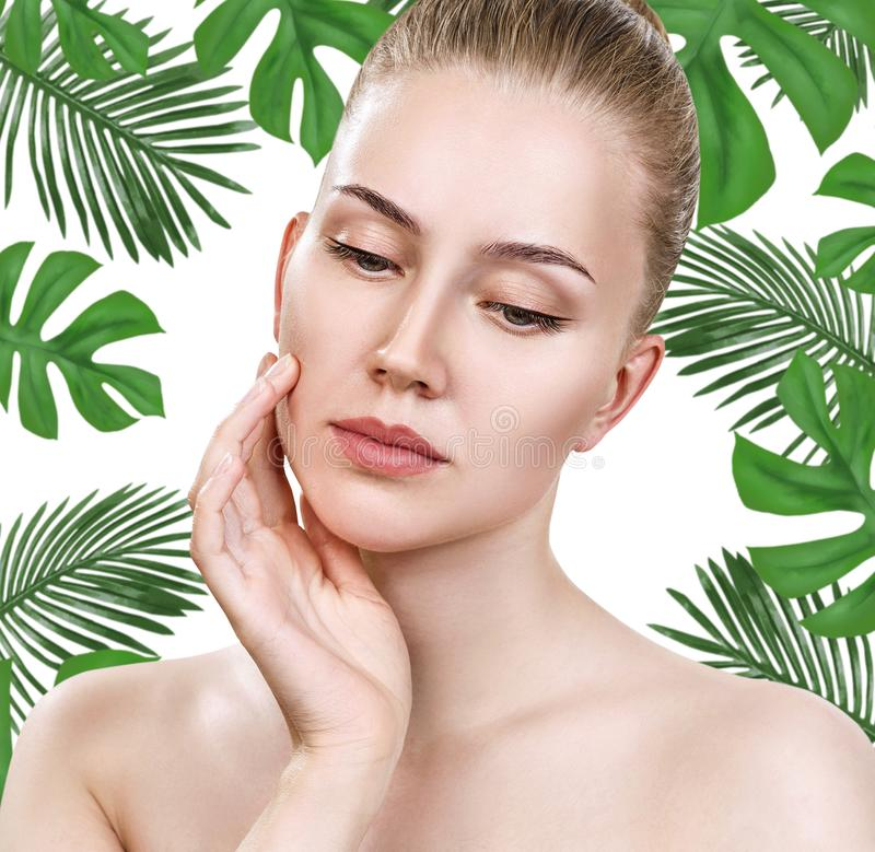 Young beautiful woman face among green palm leaves. stock photos