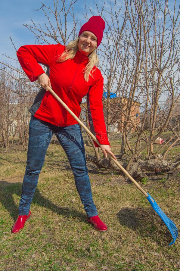 Young beautiful woman farmer cleans rake dry grass, wearing red jacket, boots and hat, vertical photo royalty free stock image