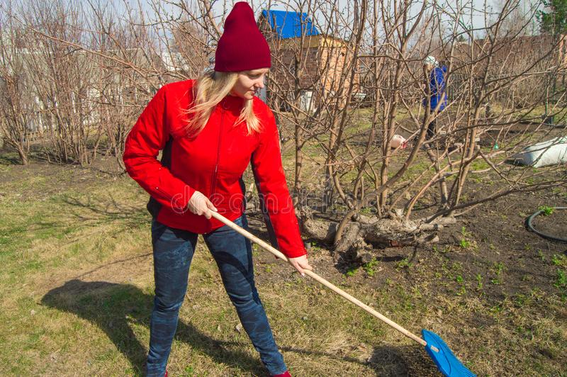 Young beautiful woman farmer cleans rake dry grass, wearing red jacket, boots and hat stock photography