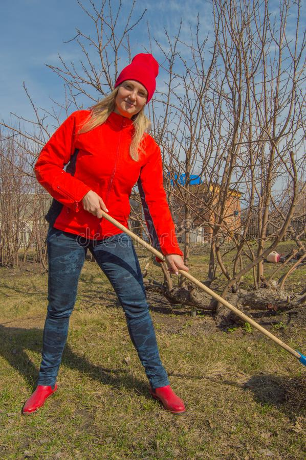 Young beautiful woman farmer cleans rake dry grass, wearing red jacket, boots and hat, vertical photo royalty free stock photos