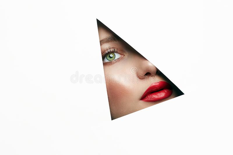 Young beautiful woman. female face with makeup into paper hole. Make-up artist concept. arrows on the eyes royalty free stock photo