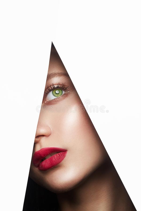 Young beautiful woman. female face with makeup into paper hole. Make-up artist concept. arrows on the eyes royalty free stock images