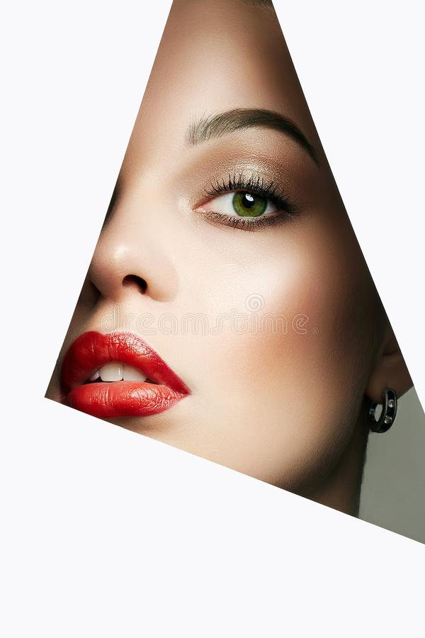 Beautiful woman. female face with makeup into paper hole. Young beautiful woman. female face with makeup into paper hole. make-up artist concept. arrows on the royalty free stock photography