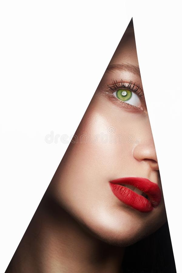 Young beautiful woman. female face with makeup into paper hole. Make-up artist concept. arrows on the eyes stock images