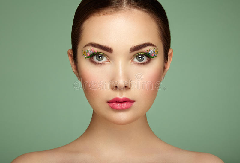 Young beautiful woman with flower makeup eyes stock photo
