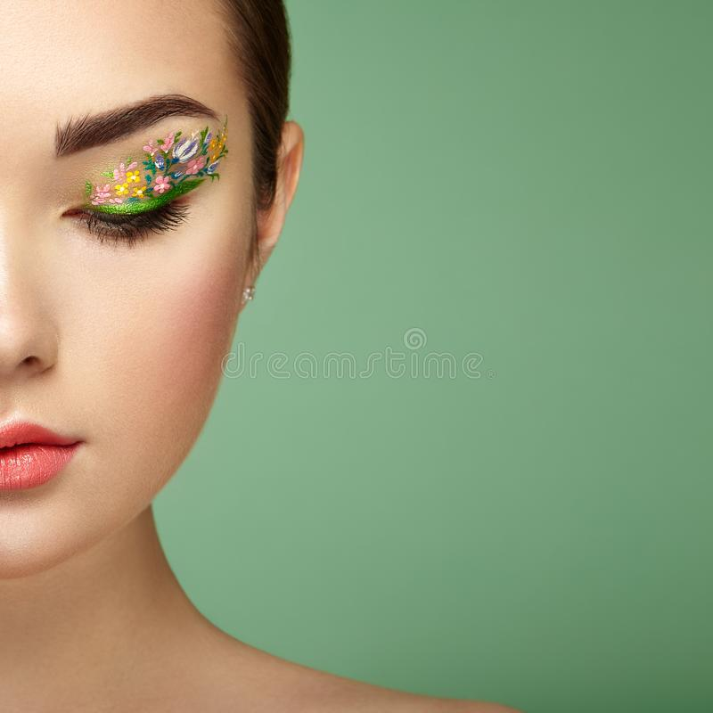 Young beautiful woman with flower makeup eyes. Spring makeup. Beauty fashion. Eyelashes. Cosmetic Eyeshadow. Make-up detail. Girl on green background stock photo