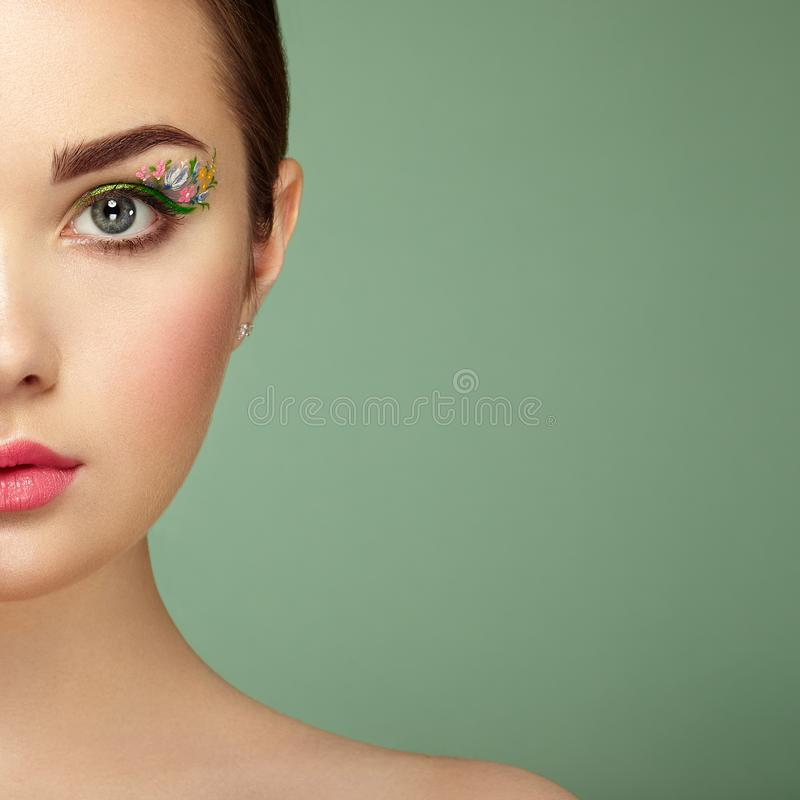 Young beautiful woman with flower makeup eyes. Spring makeup. Beauty fashion. Eyelashes. Cosmetic Eyeshadow. Make-up detail. Girl on green background stock photos