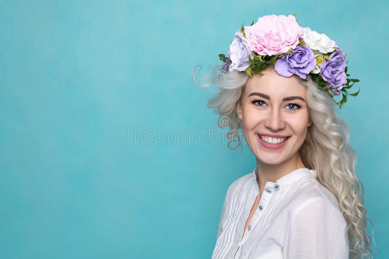 Young Beautiful Woman in Flower Wreath with Wavy Blond Hair. Spring. Studio. Copy Space royalty free stock image