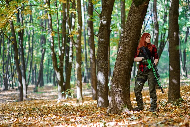 Young beautiful woman in the forest with rifle royalty free stock photos