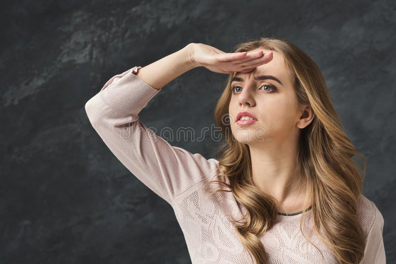 Young beautiful woman gazes into distance,. Young beautiful woman gazes into distance. Beautiful girl looking forward, gray studio background royalty free stock image