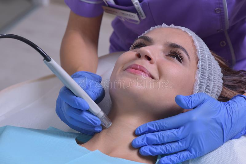 Young beautiful woman gets professional skin treatment royalty free stock photos