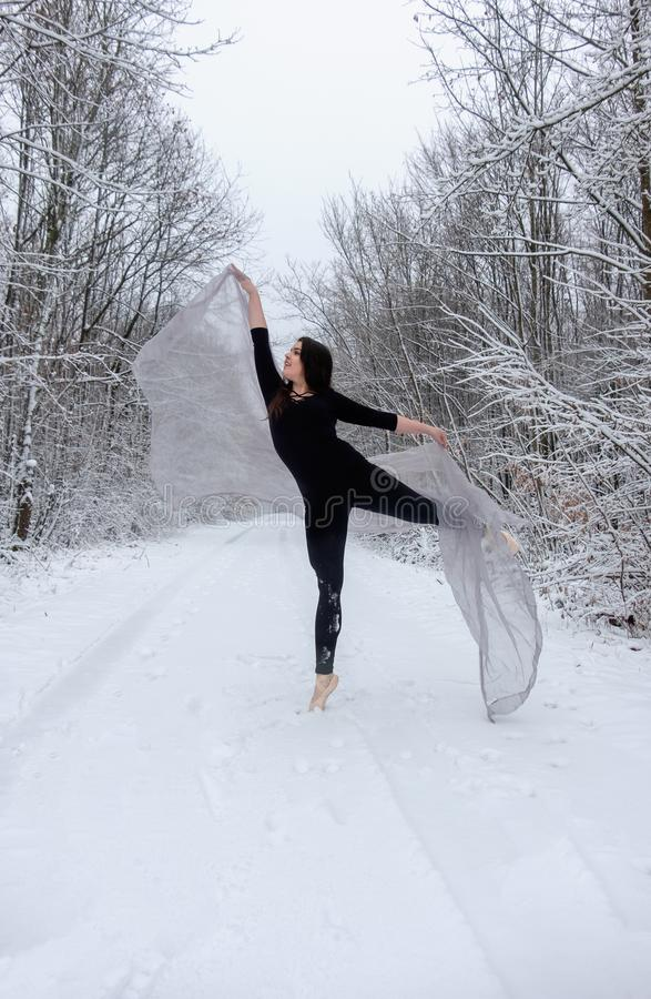 Young beautiful woman girl ballet presents herself in snowy winter forest and dances on toe top stock photos