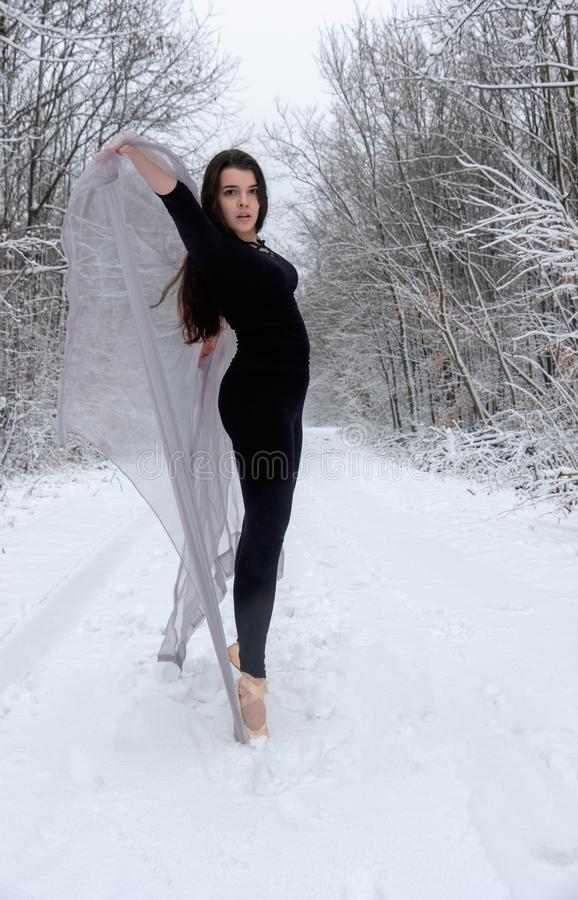 Young beautiful woman girl in snowy winter forest is stretching and standing on toe top in ballet shoes royalty free stock photo