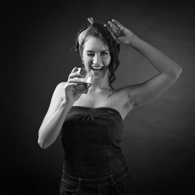 Black and white portrait of a young beautiful woman with glass of whiskey