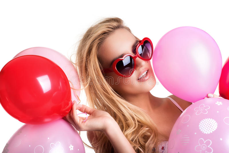 Young beautiful woman with glasses holding red pink balloons, va royalty free stock photo