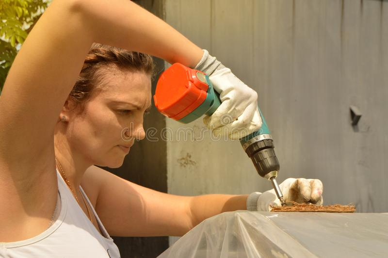Young beautiful woman in gloves uses drill in her garden stock photos