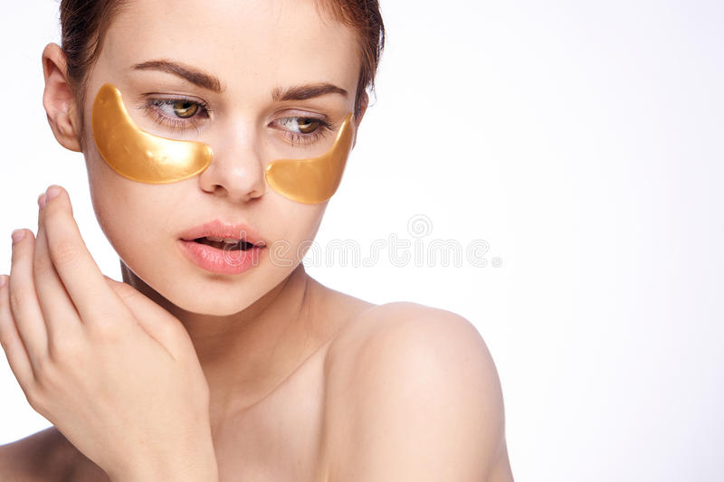 Young beautiful woman in gold patches for eyes on white isolated background, face skin care stock image