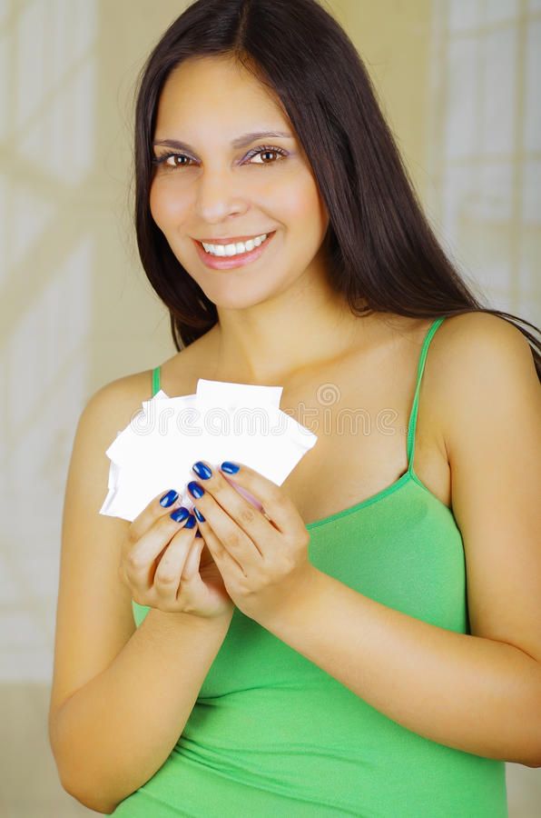 Young beautiful woman with a green blouse holding a couple of hygenic towels royalty free stock images