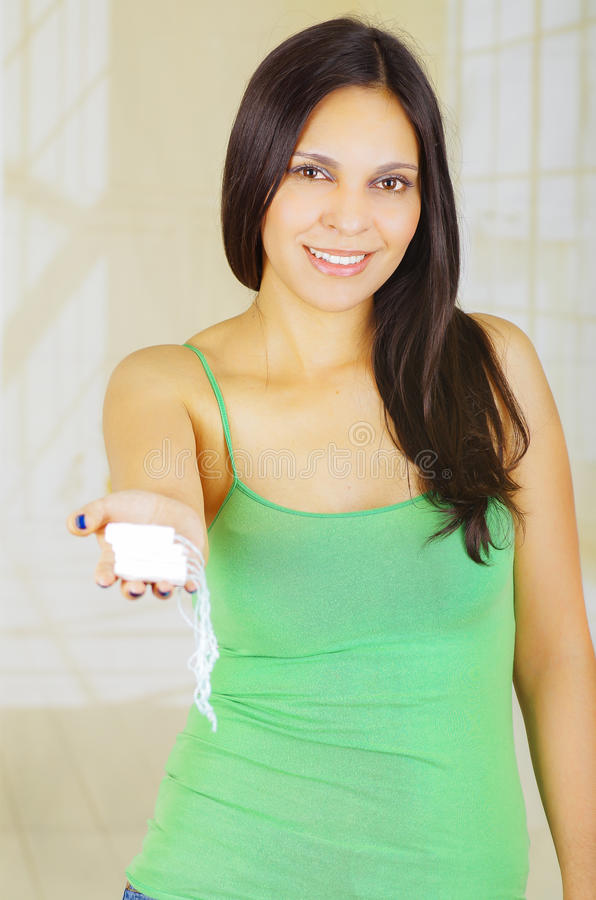 Young beautiful woman with a green blouse holding a hygenic towel with one hand and pointing in front of herself stock image