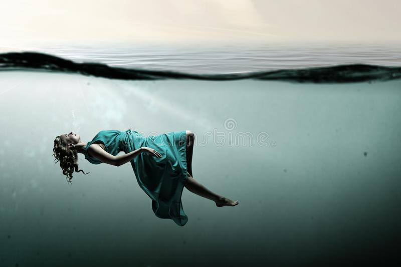 Woman dancer in clear blue water stock image